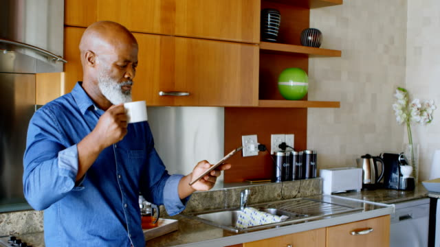 senior man using digital tablet while having black coffee in kitchen 4k - cinquantenne video stock e b–roll