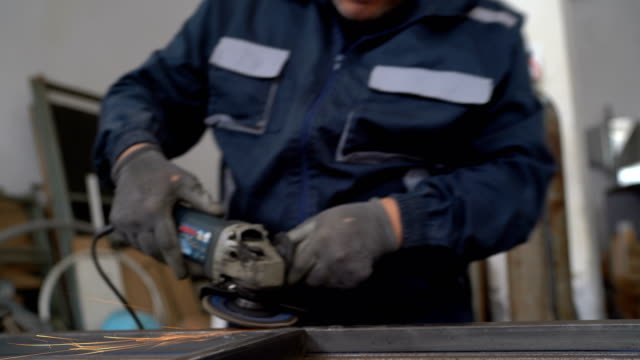 Senior man using electric grinder in workshop - vídeo