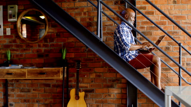 senior man using laptop on stairs in living room 4k - cinquantenne video stock e b–roll