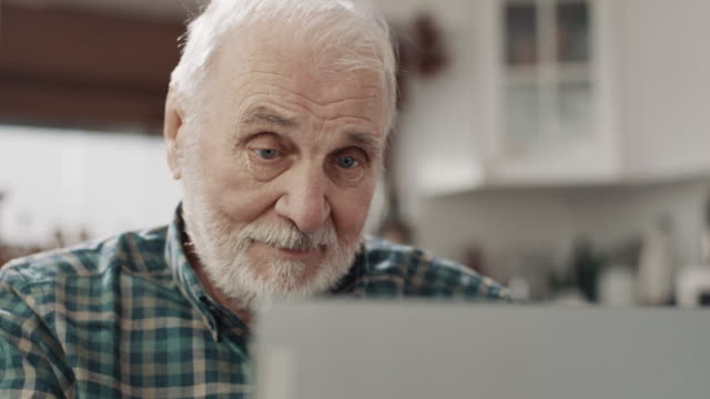 vídeos de stock e filmes b-roll de senior man using laptop - old men window