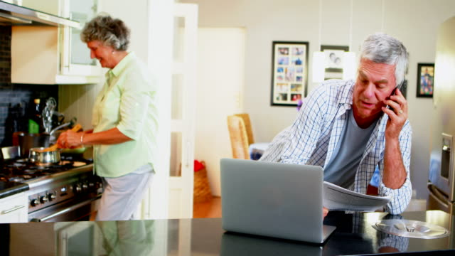 Senior man using laptop while woman cooking in background 4k video