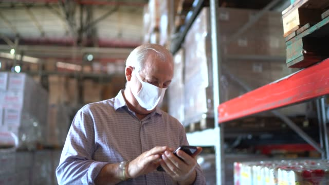 senior man using mobile phone at warehouse - with face mask - prodotti supermercato video stock e b–roll