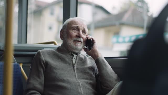 Senior man using phone in the bus