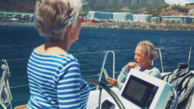 Senior man using phone while woman steering yacht