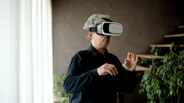 Senior man using virtual reality glasses video