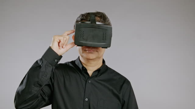 senior man using virtual reality headset, turn it on, smile, isolated in grey background. asian man in black shirt. - top nero video stock e b–roll