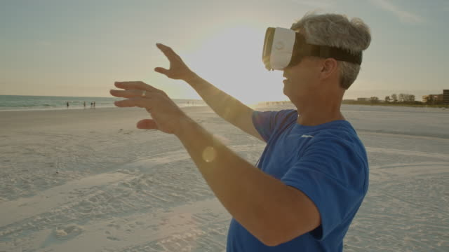 senior man virtual reality headset googles gaming florida beach - google filmów i materiałów b-roll