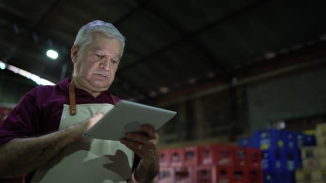 vídeos de stock e filmes b-roll de senior man walking and using digital tablet at warehouse - supermarket worker
