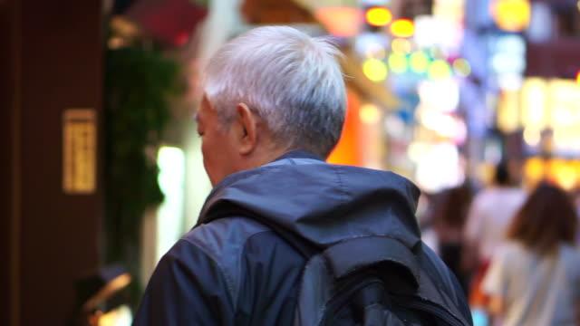 Senior man walking in Tokyo night street district. Tourist walking around Japan video