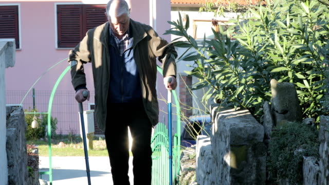 Senior Man Walking on Frontyard Stairs With Crutches video