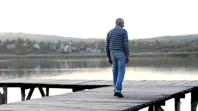 Senior man walking on wooden lake pier at autumn day video