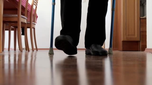Senior Man Walking Past Camera With Crutch Senior Man Walking Past Camera With Crutch. crutch stock videos & royalty-free footage