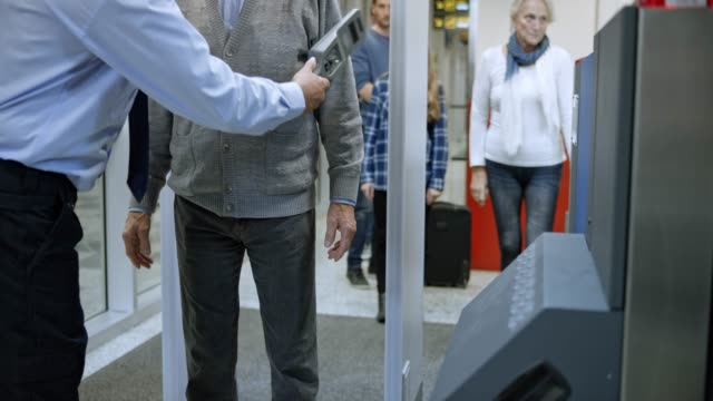 Senior man walking through a metal detector at the airport and being scanned by a handheld metal detector video