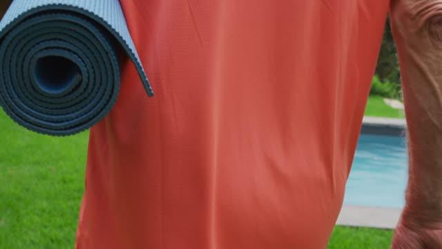 senior man walking with a yoga mat - materassino ginnico video stock e b–roll