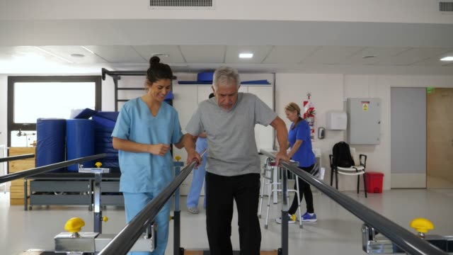 senior man walking with difficulty using the parallel bars and therapist standing next to him helping - fisioterapia video stock e b–roll