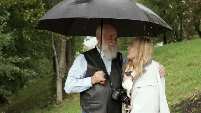 Senior man walks with young woman under umbrella in park video