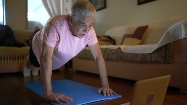 시니어 남자 보고 체육관 클래스 에 노트북 과 하기 운동 에 홈 - 동작 정지 스톡 비디오 및 b-롤 화면