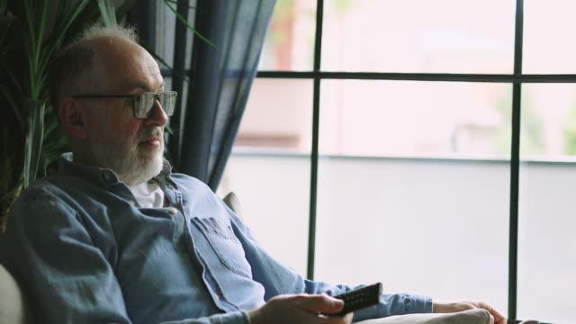 Senior man watching TV at home Senior man watching TV at home baby boomers stock videos & royalty-free footage