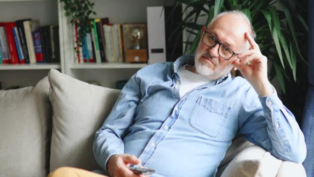 senior man tittar på tv hemma - mänsklig ålder bildbanksvideor och videomaterial från bakom kulisserna