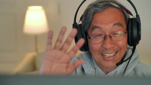 自宅でパソコンを介して手を振ったり、ビデオ通話で話したりするシニアマン。ヘッドホンを介してビデオ通話を再生するシニア男性。コンピュータ上の友人と通信する肯定的な先輩男性。� - ゲーム ヘッドフォン点の映像素材/bロール