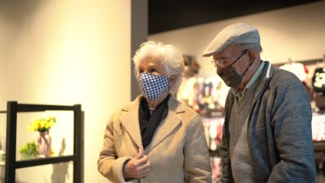 vídeos y material grabado en eventos de stock de hombre de la tercera edad usando máscara facial ayudando a la esposa a probarse abrigos en una tienda de segunda mano - abrigo