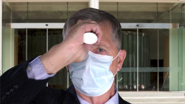 Senior man wearing face mask taking his temperature to check for virus at office entrance - video