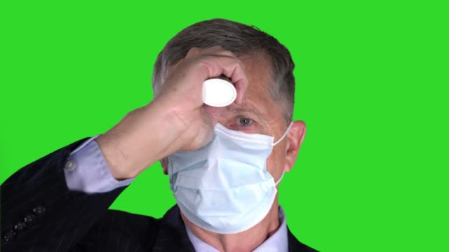 Senior man wearing face mask taking his temperature to check for virus against chroma key green screen - video