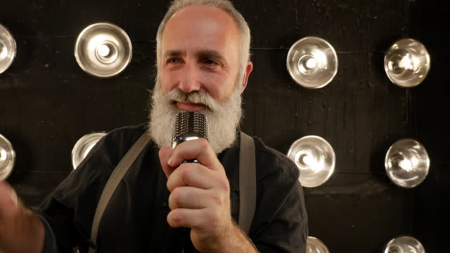 senior man with a beard singing with a microphone