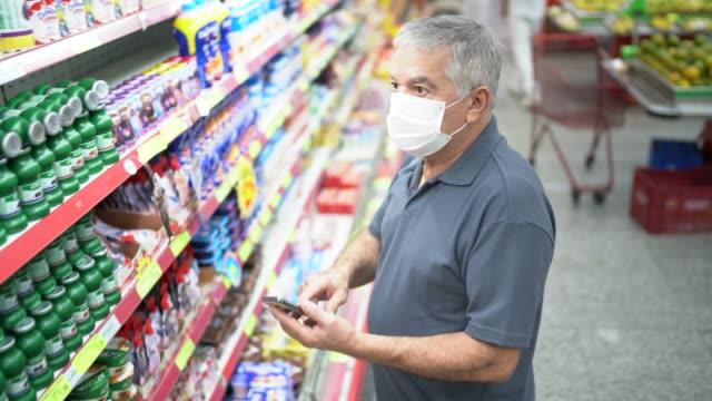 senior mann mit einweg-medizinmaske und seinem handy einkaufen im supermarkt - smartphone mit corona app stock-videos und b-roll-filmmaterial