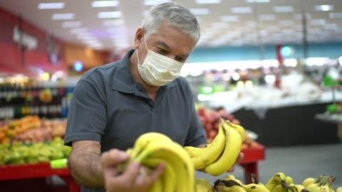 vidéos et rushes de homme aîné avec le magasinage jetable de masque médical dans le supermarché - faire les courses