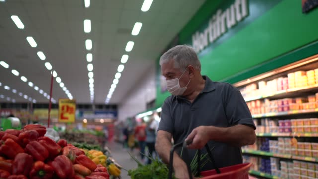 Senior man with disposable medical mask shopping in supermarket video