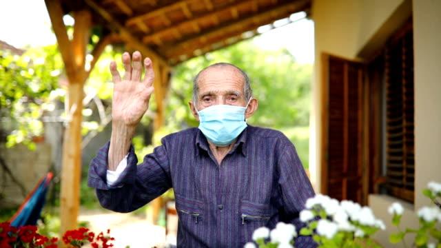 vídeos de stock e filmes b-roll de senior man with face mask on the balcony - old men window
