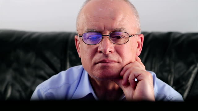 Senior man with glasses watching TV video