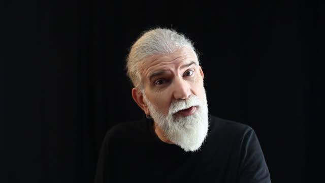 Senior man with gray hair and beard talking to camera video