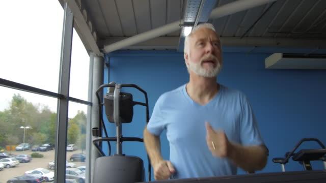 Senior man with grey hair and beard on running machine video