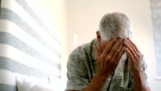 Alter Mann mit Kopf weh tut sitzen auf dem Bett – Video