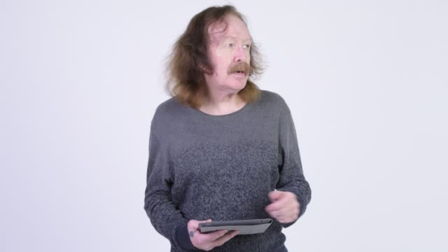 Senior man with long hair and mustache using digital tablet
