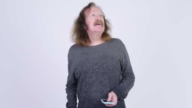 Senior man with long hair and mustache using phone