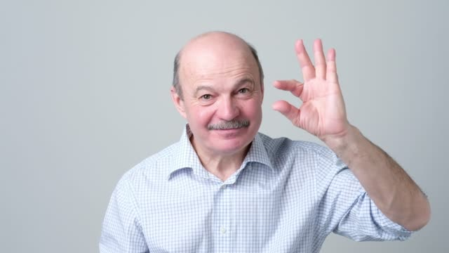 senior man with mustache showing something small with fingers. - baffo peluria del viso video stock e b–roll
