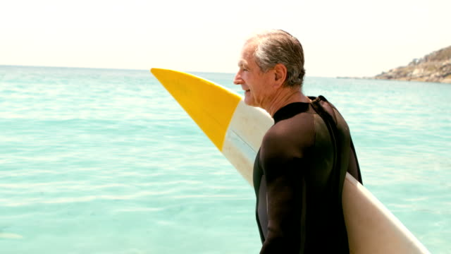 Senior man with surfboard posing video