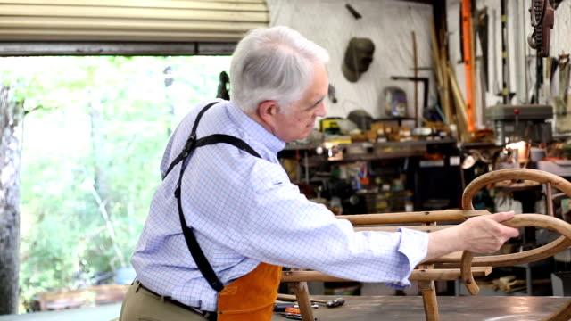 年配の男性は、彼のワーク ショップで一人での作業します。 - 大工点の映像素材/bロール