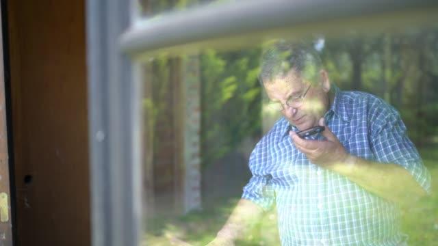 vídeos de stock, filmes e b-roll de homem sênior que trabalha e que usa o móbil na garagem - mobile