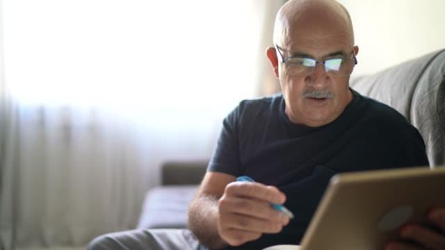 vídeos de stock, filmes e b-roll de idoso trabalhando / fazendo algumas anotações em casa - escrever