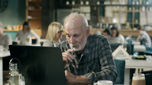 Senior man working on laptop and wapping in restaurant video
