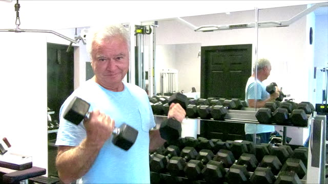 Senior man working out at the gym, lifting handweights video