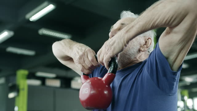 Senior man working out with a kettle bell
