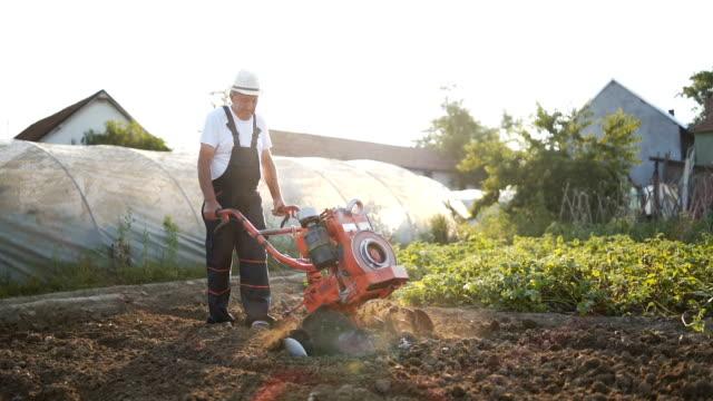 Senior man working with cultivator Senior man working with cultivator plow stock videos & royalty-free footage