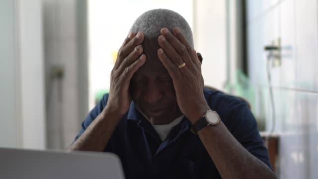 Senior man worried working at laptop