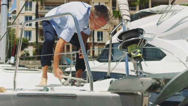 Senior man wrapping rope on bollard in yacht
