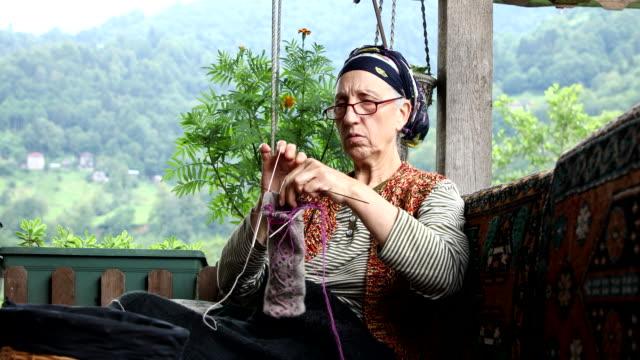 Senior mature countrywoman knitting  on sofa
